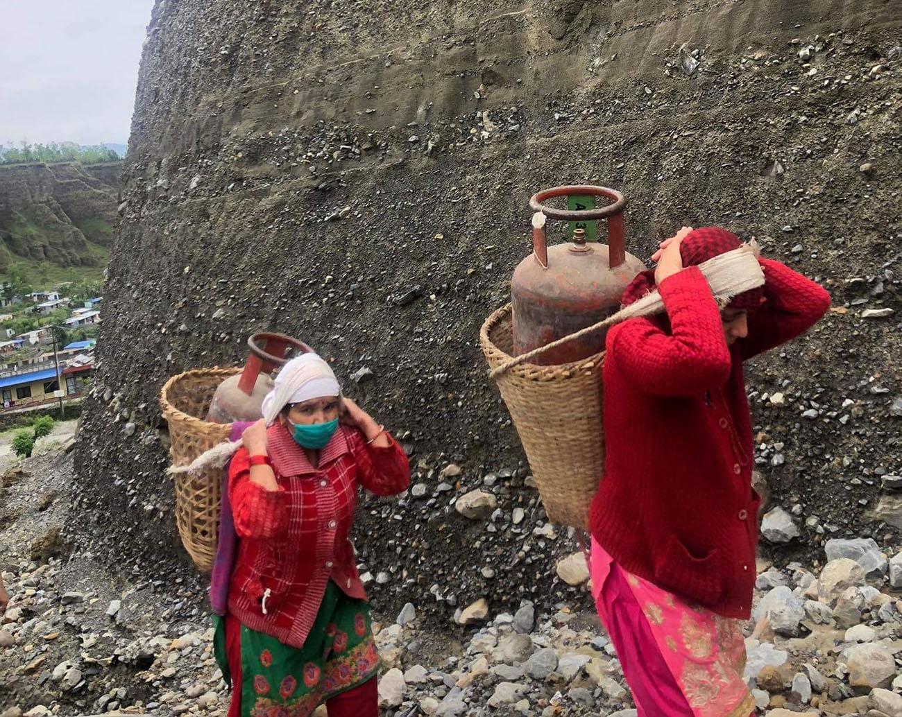 पोखरा महानगरपालिका–१७ मतगौडामा खाली सिलिन्डर डोकोमा बोकेर बजारतिर जाँदै महिला । तस्वीरः राधिका कँडेल/रासस